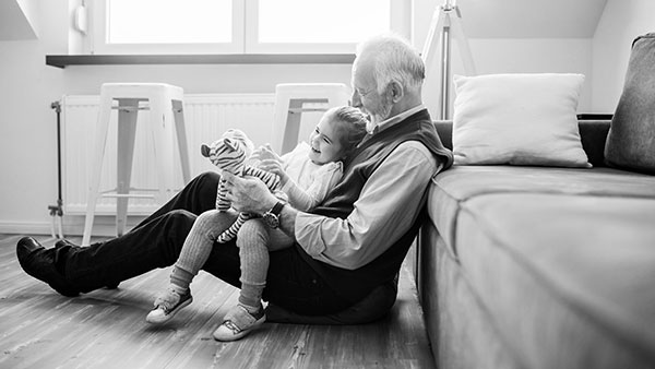 Grandad plays with his granddaughter in a warm house heated by Sainsbury energy