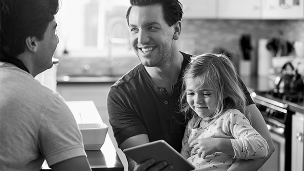 Sainsbury's energy customer holds his daughter on his lap while looking at the energy app.